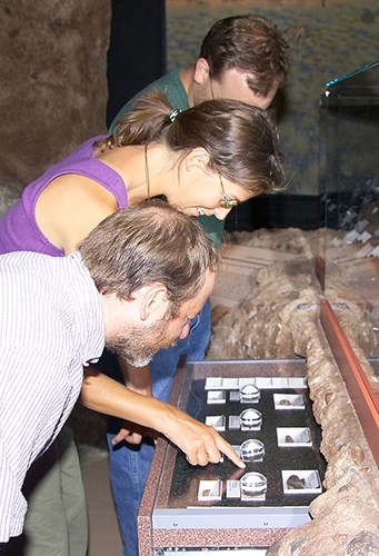 Three adults look at the fossils on display in the drawers at the visitor center. The fossils have magnification lens on them to make them easier to see the details. One points to a center fossil.
