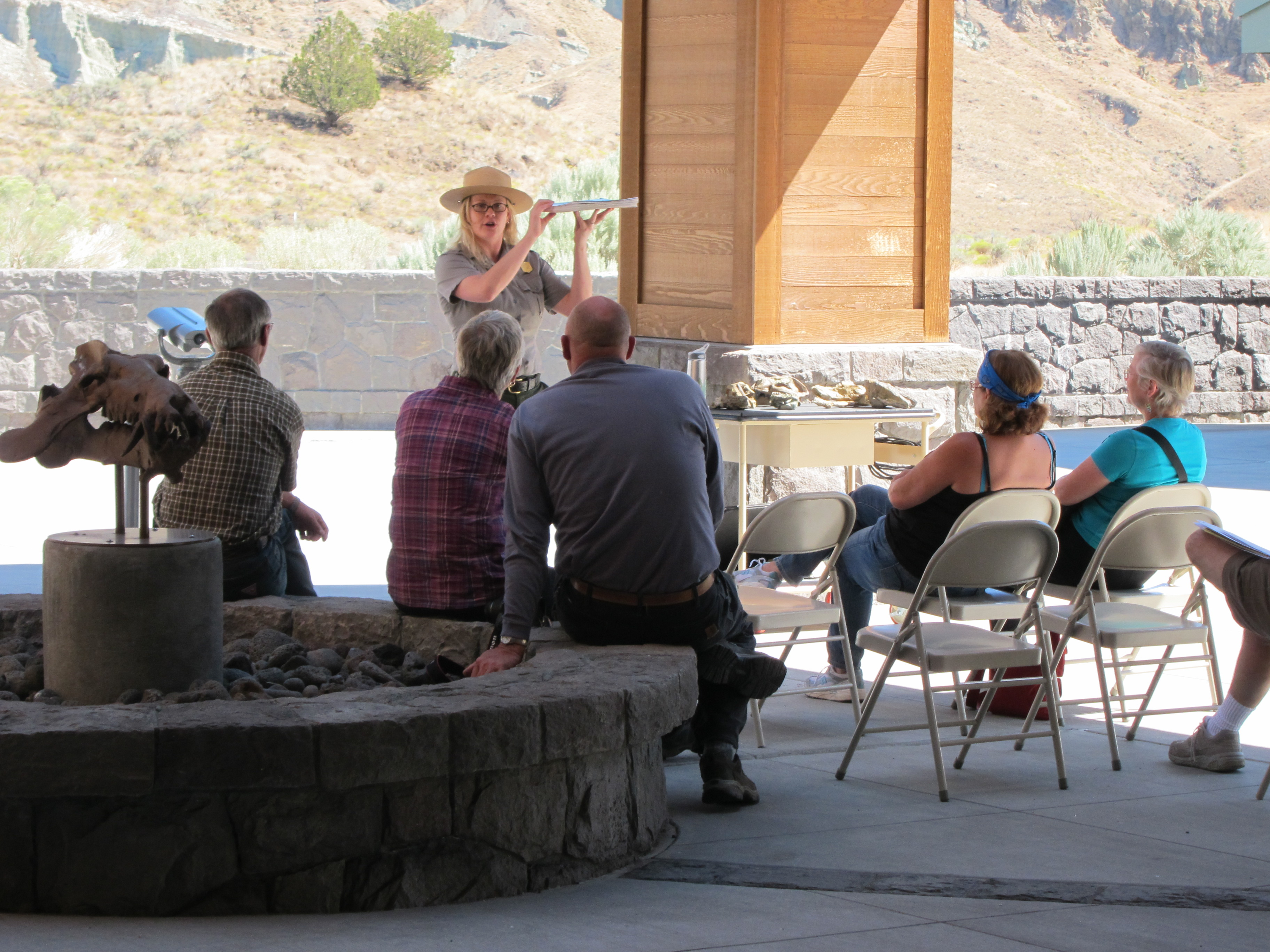 A park ranger holds up a skeleton as she discusses to an audience, the ancient animals found at John Day Fossil Beds.