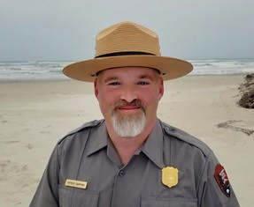 Superintendent Patrick Gamman image from bust up in his Park Service uniform and flat-hat taken in front of a sandy beach.