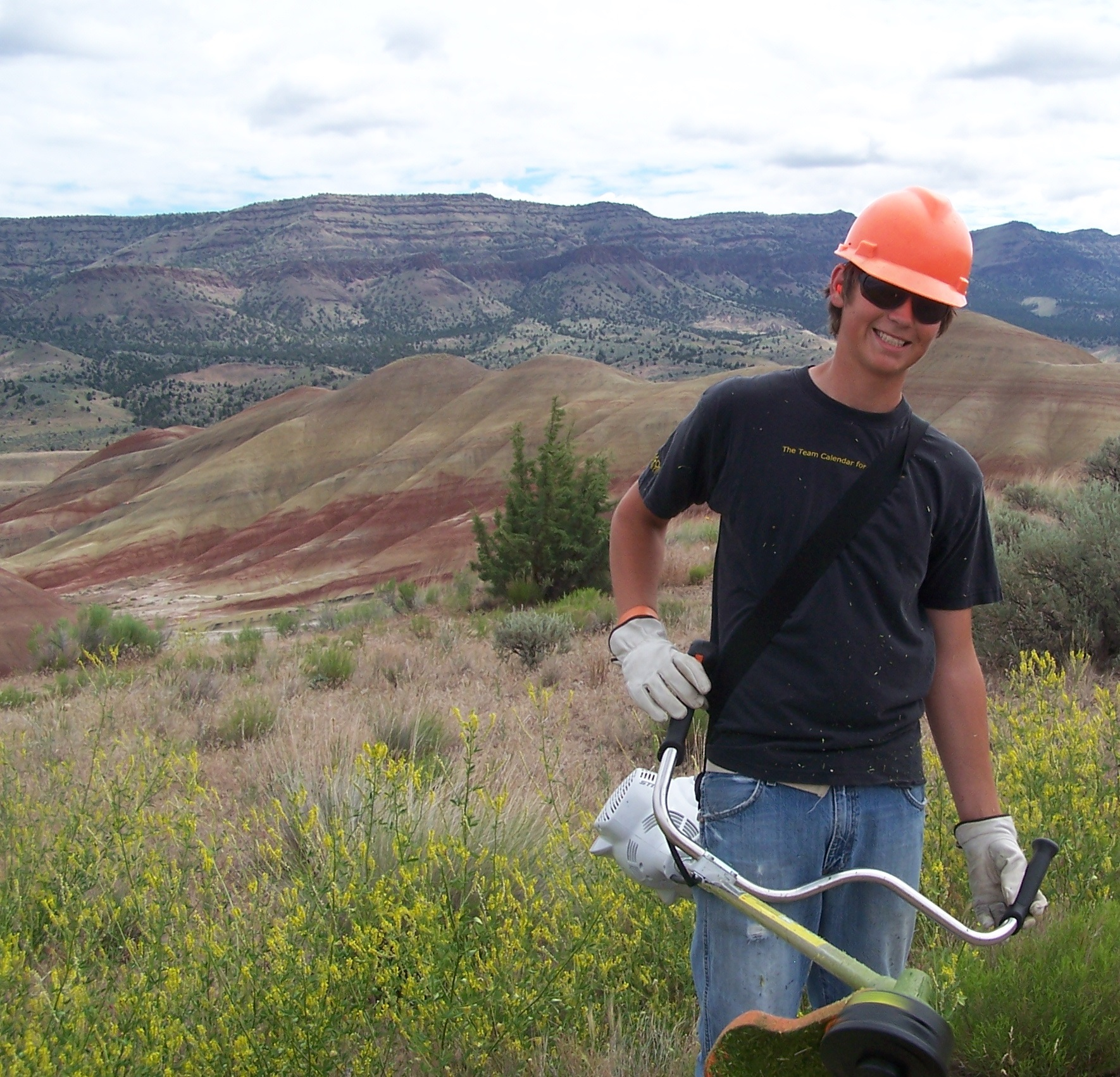 A teenager in an orage hard hat stands in the right foreground holding a weedeater. The striped hills of the Painted Hills can be seen in the right and middle of the photgraph in the background.