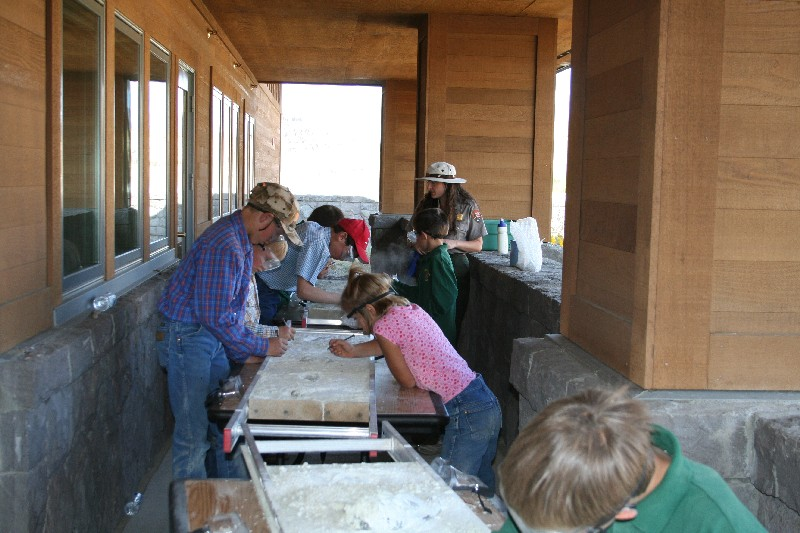 "Students examine the ""fossils"" in a simulated dig outside of the Thomas Condon Paleontology Center."