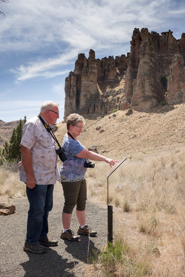 Two people read a sign along a trail. A large cliff dominates the skyline behind them.