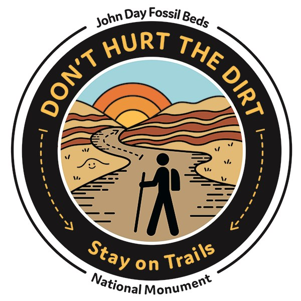 The images says Don't Hurt the Dirt Stay on Trails with a person hiking on the trails at Painted Hills