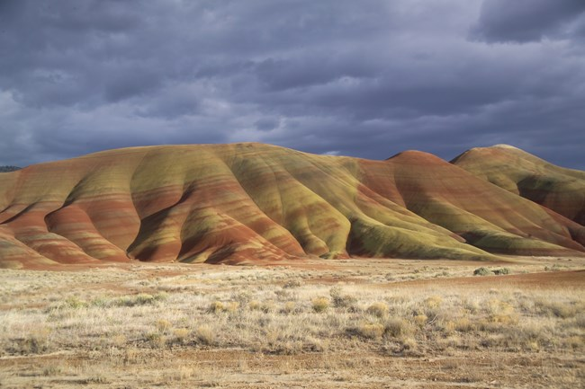 A photo of the Painted Hills taken from the road. Stormy grey skies dominate the background