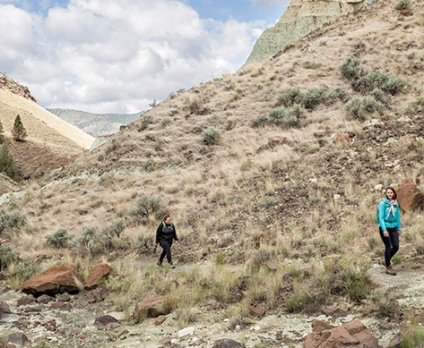 Two hikers on the Blue Basin trail are six feet apart from each other, demonstrating social distancing.