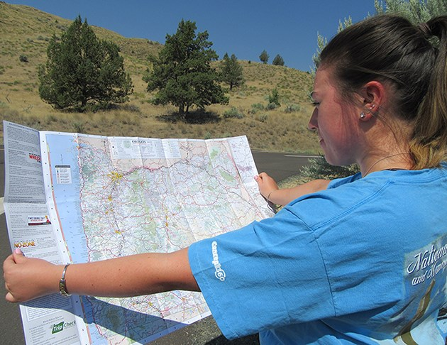 A woman holds up a paper map of Oregon to orient her location.
