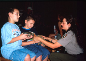 Image of a park ranger showing fossils to some children.