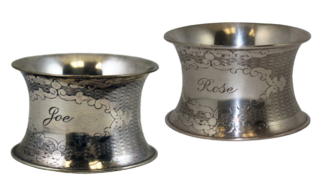 A pair of silver napkin rings engraved with the names