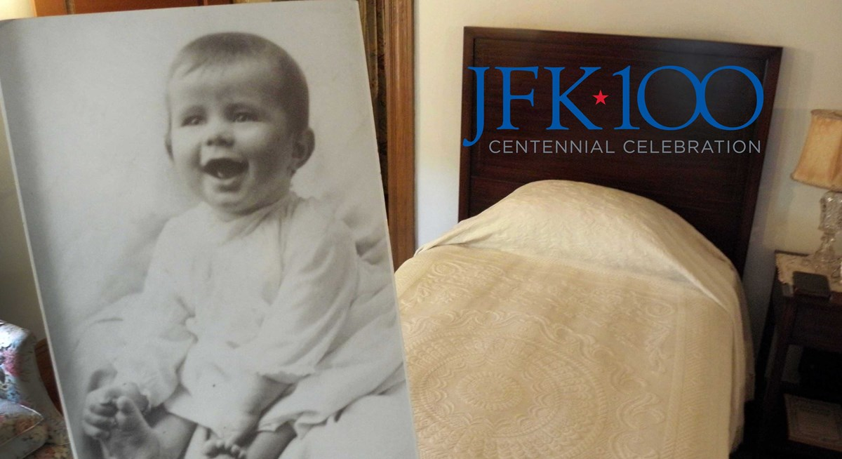 Photo of JFK as baby in front of birth bed