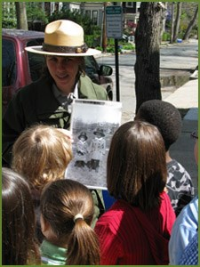 A ranger shows students a photo from JFK's boyhood in Brookline