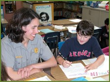 A ranger encourages a student writing an essay