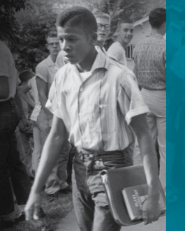 An African-American student with books under his arm walks through a crowd of white students.