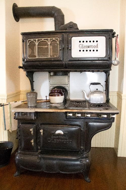 A Glenwood gas and coal burning stove.  The stove is black and has a variety of oven doors.  There are several items atop the stove, including a silver kettle and ceramic bean pot.