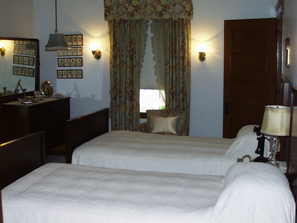 Two twin beds covered with white embroidered spreads fill the room.  A window and baby photos are at the far end of the room.  A dark wooden dresser stands to the left of the beds.
