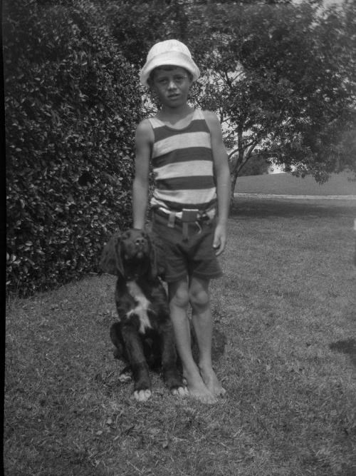 A young JFK stands on grass with his dog.  The photo is black and white.  JFK is wearing a striped shirt, shorts, and a sun hat.  The dog is a black spaniel.