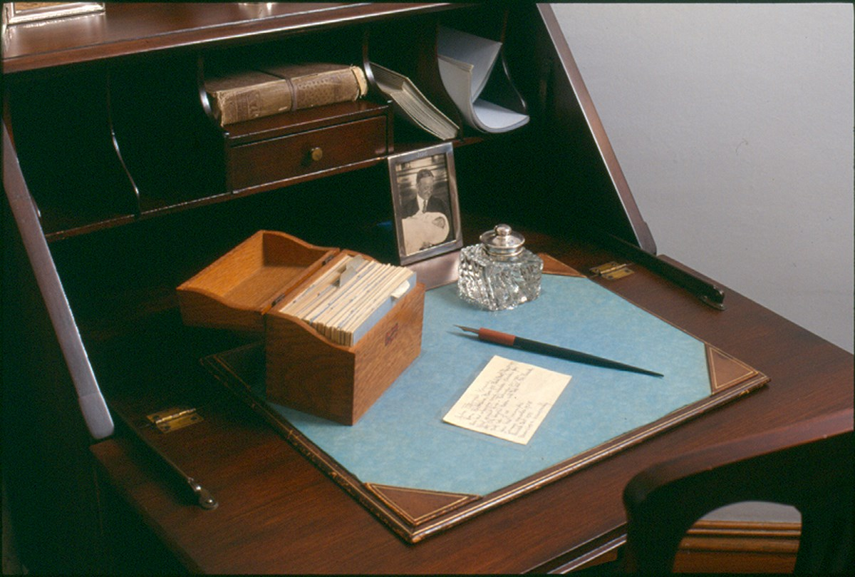 A brown wooden desk.  On the top sits a wooden card file box, a card on JFK, a fountain pen, ink well, and a photograph of Rose's father, John F. Fitzgerald, holding Joe Jr.