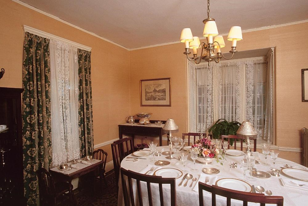 A large dinner table sits in the center of the room.  It is topped with fine dinnerware.  Above the table hangs a chandelier.  By the left window, sits a children's table.