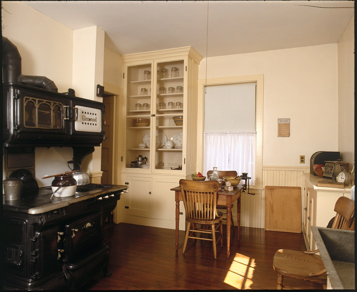 A black Glenwood coal and gas burning stove is on the left.  A white cabinet with glass doors houses cookware.  A small wooden table sits at the back of the room.  On the right is a counter with a soapstone sink.