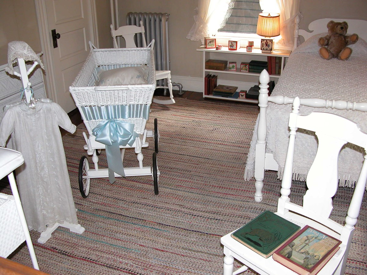 A white bassinet and christening gown at the left of the photo.  A white chair with two children's books is at the right forefront.  Behind the chair is a white twin bed with a teddy bear on top.  A white bookcase sits to the left of the bed.