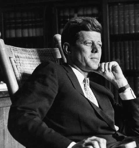 President Kennedy is seated sideways in a rocking chair looking ahead while resting his chin in his hand.  He looks like he's deep in thought.