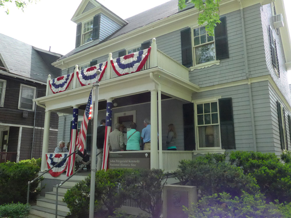 Visitors listen to a ranger on the front porch of John F. Kennedy's birthplace on his birthday.