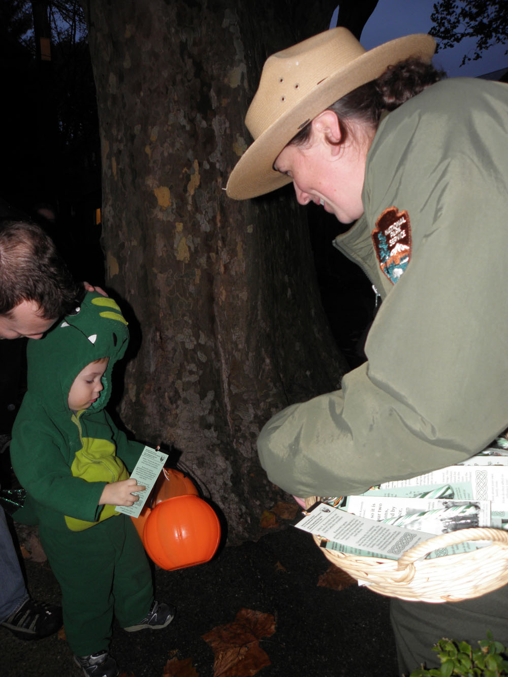 A ranger hands a child dressed as an alligator a Halloween treat.