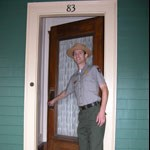 A Park Ranger opens the front door of 83 Beals Street, where John F. Kennedy was born.