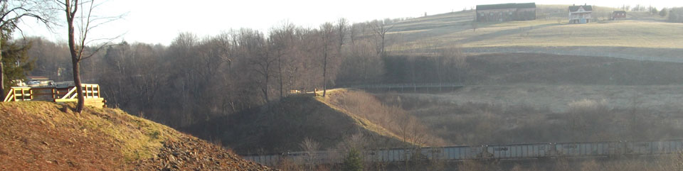 A view of the South and North abutments of the South Fork Dam.  The Visitor Center, Unger House, and Spring House are visible in the background.  As is visible, a spur railroad line connects coal trains with the main line of the railroad.