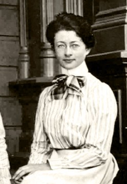Photo of Helen Muir Funk. Young woman with glasses, sitting in a dress.