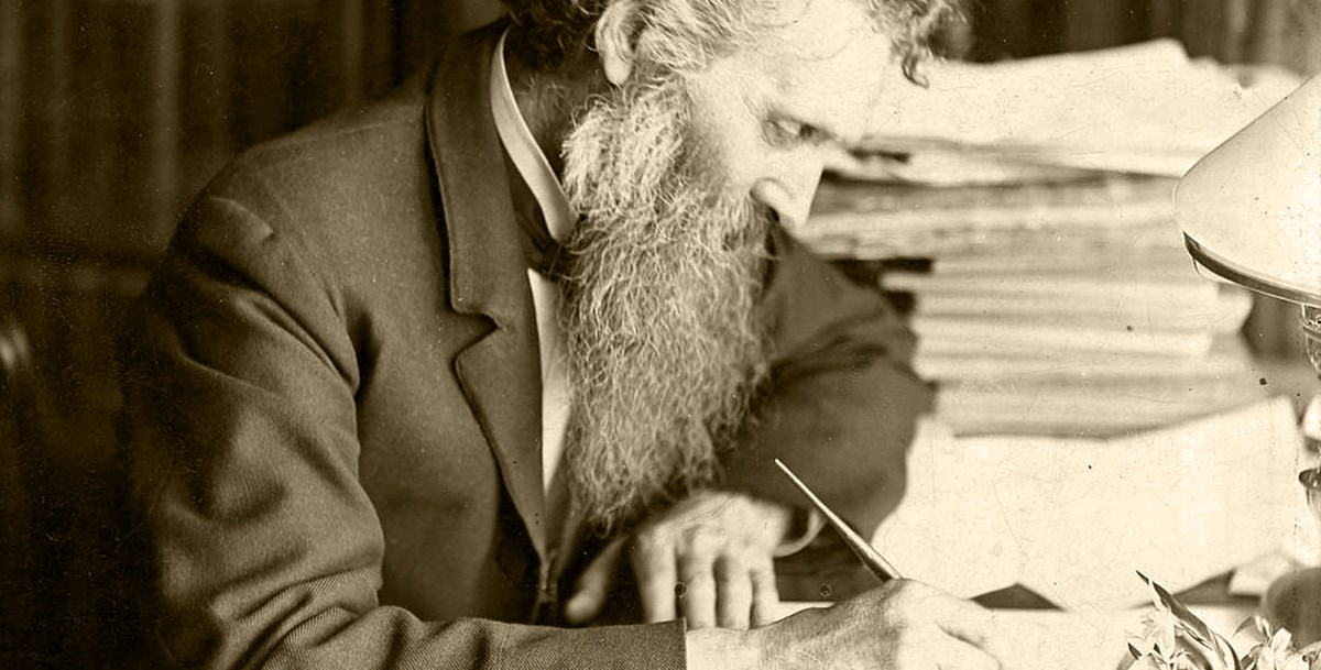 A mature John Muir, writing at his desk.
