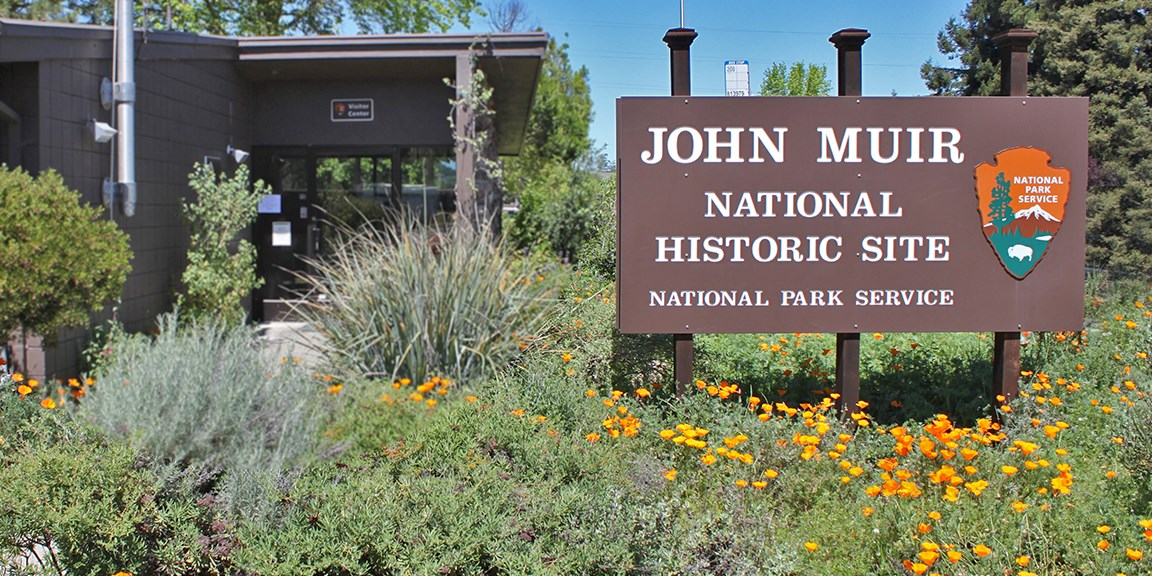 A wooden park sign, with park name, in front of the John Muir Visitor Center.