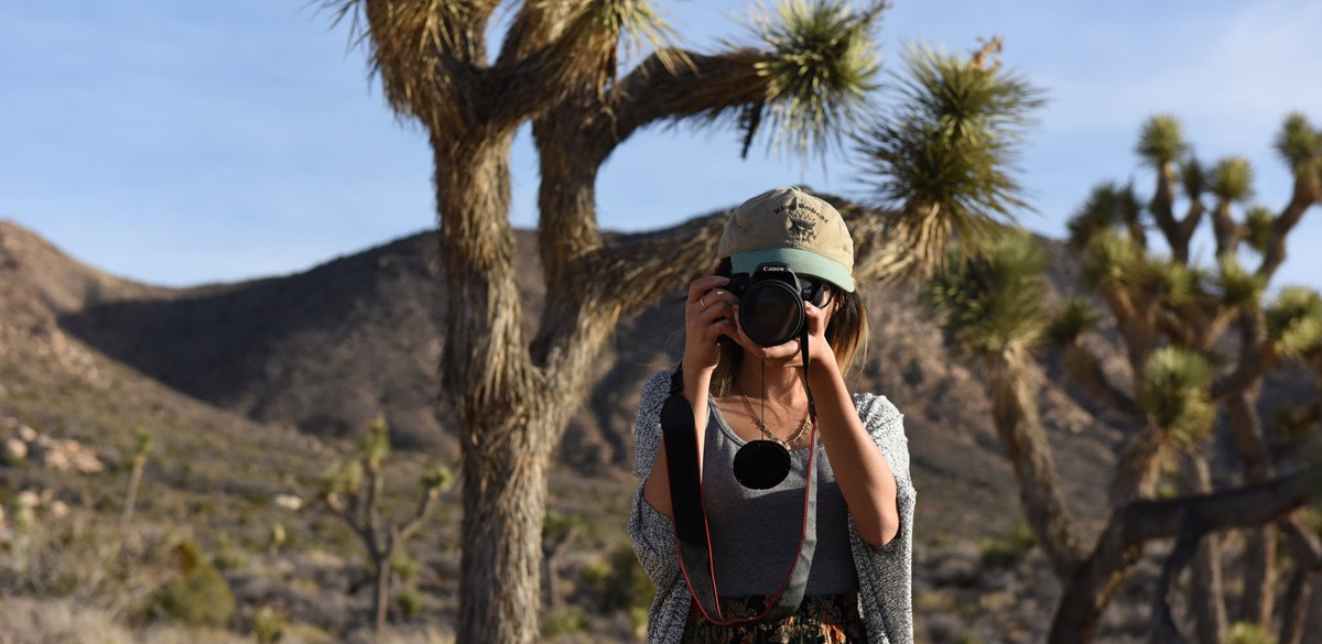 a woman wearing a hat holds a large camera to her eye pointed directly at you with mountain slopes and spindly Joshua trees behind her