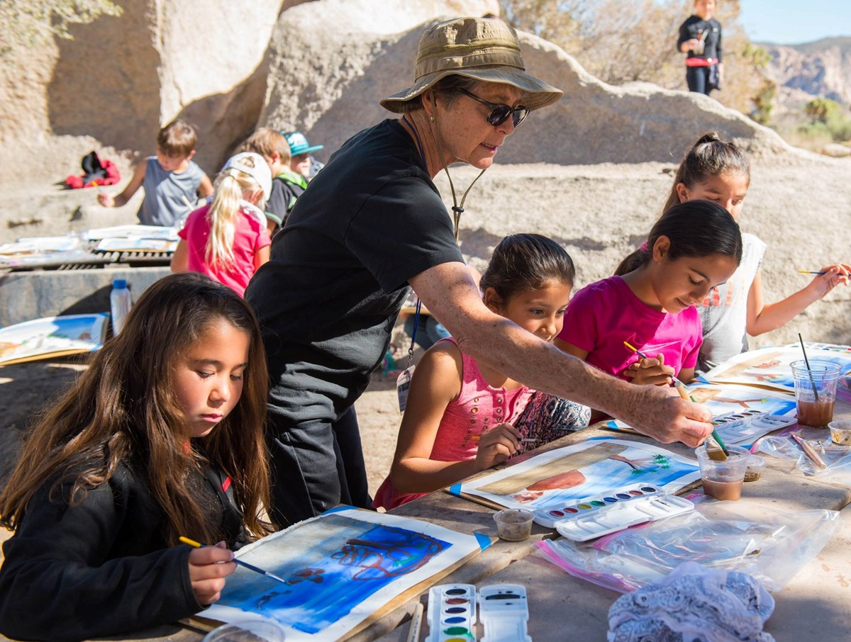 Color photograph of four children and adult artist in the foreground painting nature scenes with watercolors.  In the background other children can be seen painting and playing on large boulders.