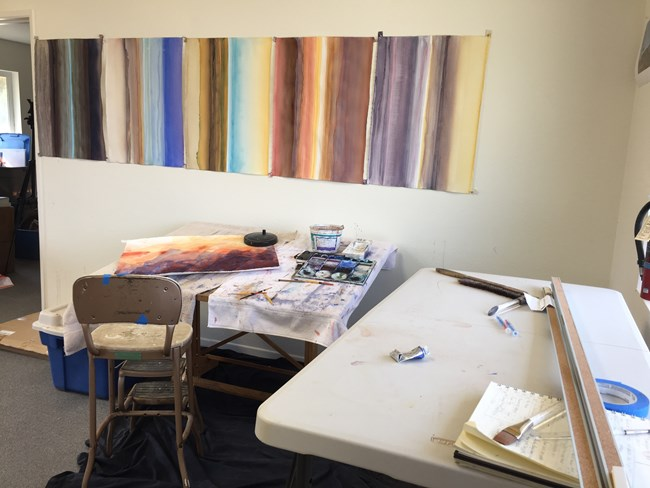 Indoor artist in residence studio.  In the foreground a white table with various art supplies.  In the back ground a painting of mountains dries on a desk and gradient artwork hangs on the wall.