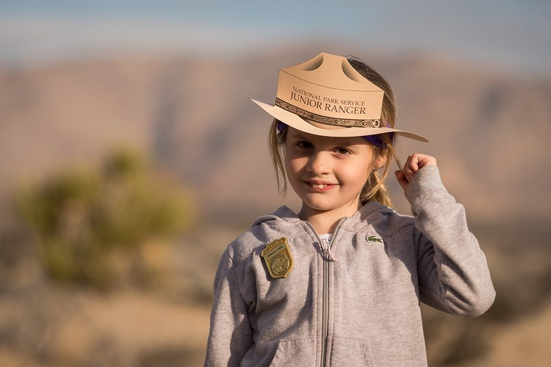 A child wearing a junior ranger hat and badge smiling at the camera