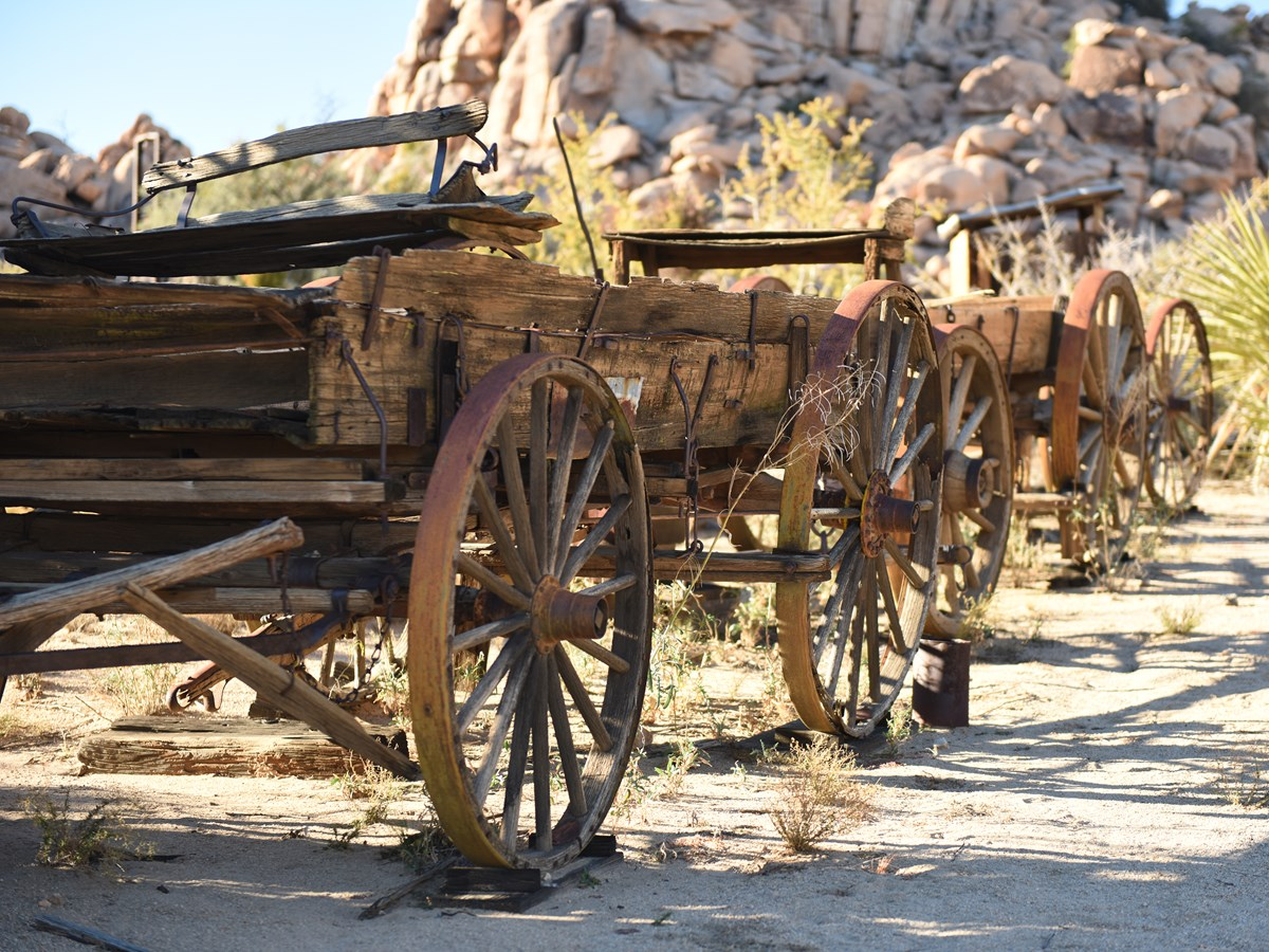 Color photo of old-time wagon wheels in a line. NPS / Hannah Schwalbe