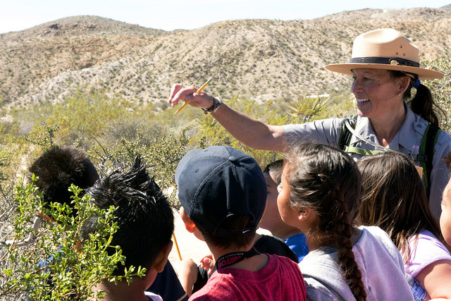 Ranger Cynthia points out a creosote bush to students on a field trip