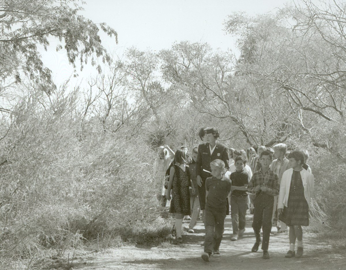 photo from the 1960s showing a group of children walking in the desert with a woman ranger