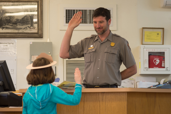 a young girl and a park ranger face each other with right hands raised
