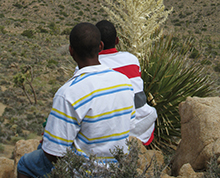 two students sit on a rock and look out over the desert