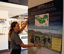 park ranger installing new wilderness exhibit on the visitor center wall