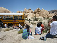 elementary school students sit outside in the park to eat lunch, with their school bus nearby