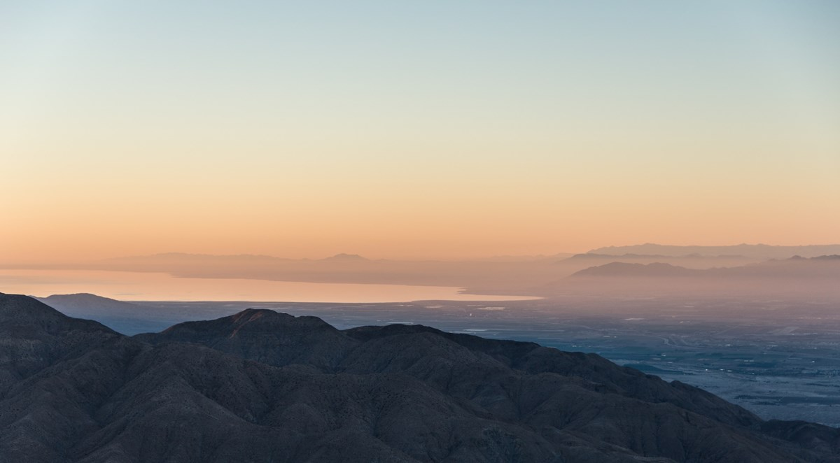 Looking out over the Salton Sea from Keys View. It is just after sunset and the light is very pink. The foreground mountains are blue.