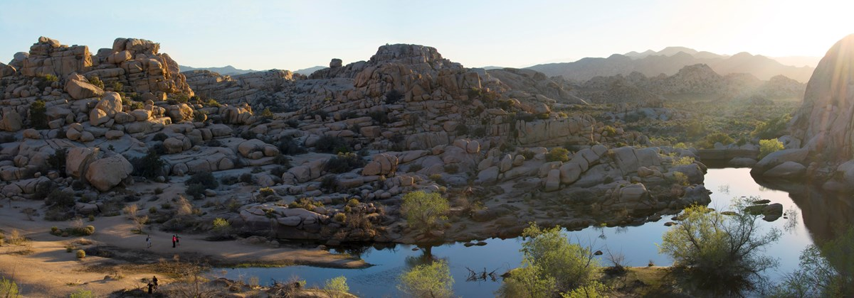 Color photo taken from above the Barker Dam area of a panoramic view at sunset. Water, piles of rocks, and some vegetation fill the area. Photo: NPS / Hannah Schwalbe
