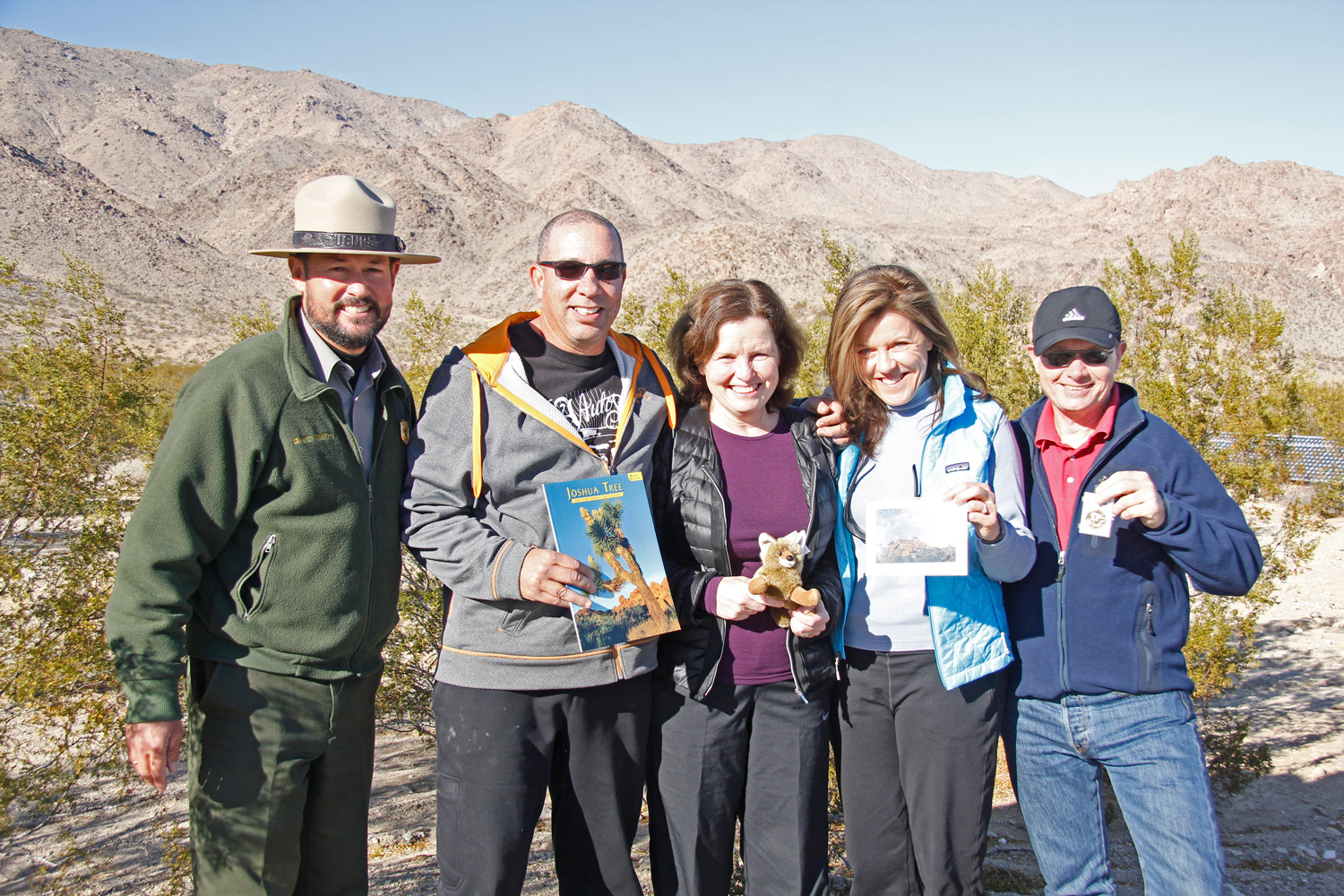 Four visitors stand with park Superintendent.