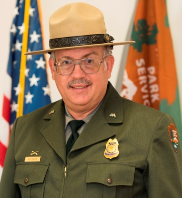 photo of park ranger in dress uniform in front of American and NPS flags