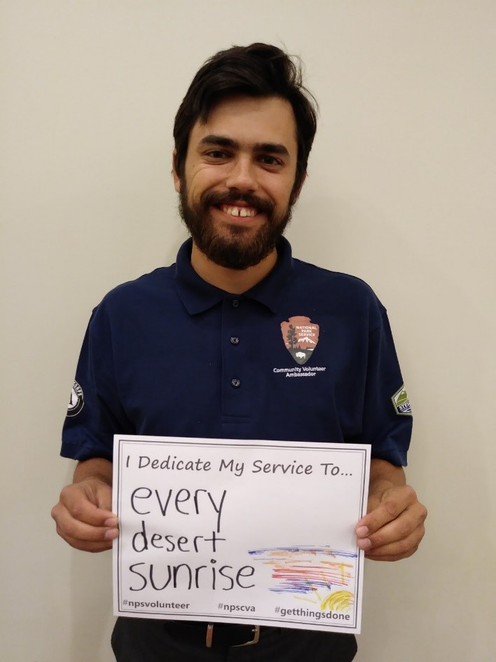 "Color photo of a man, wearing a volunteer shirt, holding a piece of paper that says ""I dedicate my service to... every desert sunrise."""