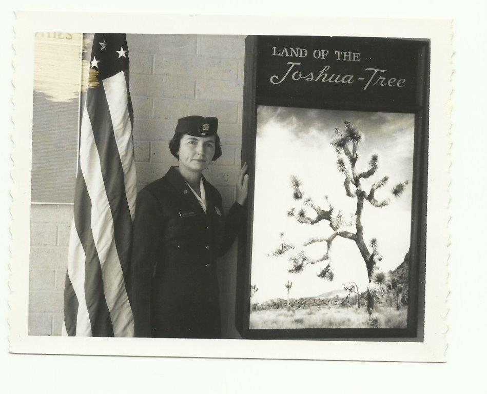 "black and white photo of a female park ranger standing next to a sign that reads ""Land of the Joshua-Tree"""