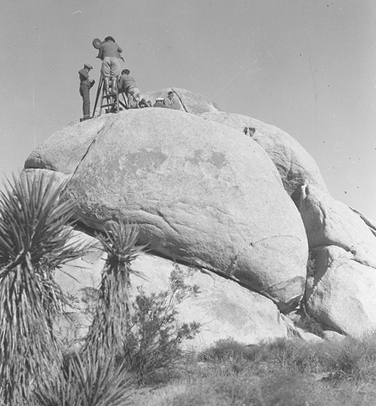A film crew set up atop boulders