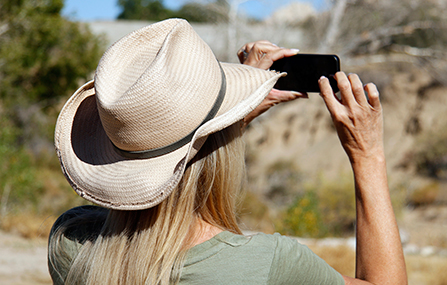 A visitor uses a smart phone to take a picture while on a Keys Ranch tour. Cell phone service is unavailable in most of the park.